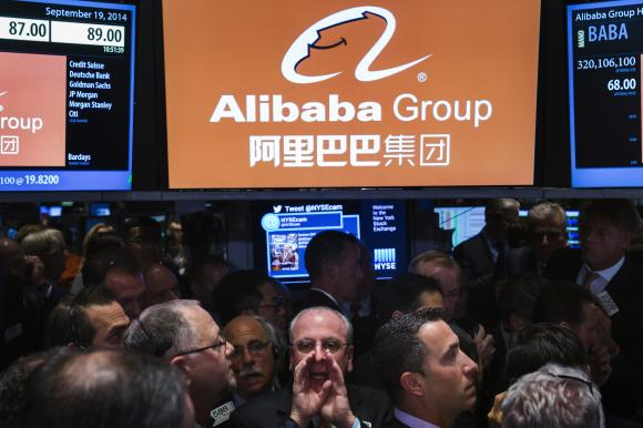 Traders work on the floor as they wait for a final price on the Alibaba Group Holding Ltd. initial public offering (IPO) under the ticker ''BABA'', at the New York Stock Exchange in New York September 19, 2014. Credit: Reuters/Lucas Jackson