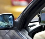 A taxi driver is reflected in a side mirror as he uses the Didi Chuxing car-hailing application in Beijing, China, in this September 22, 2015 file picture. Reuters/Jason Lee/Files